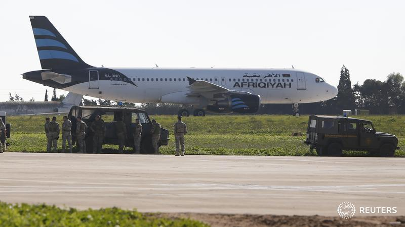 Maltese troops survey a hijacked Libyan Afriqiyah Airways Airbus A320 on the runway at Malta Airport