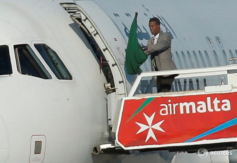 One of the hijackers of a Libyan Afriqiyah Airways Airbus A320 waves a Gaddafi-era Libyan flag at Malta Airport