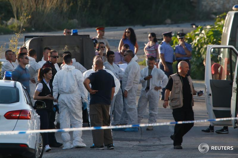 Police and forensics experts stand behind a road block after a powerful bomb blew up a car killing investigative journalist Daphne Caruana Galizia in Bidnija