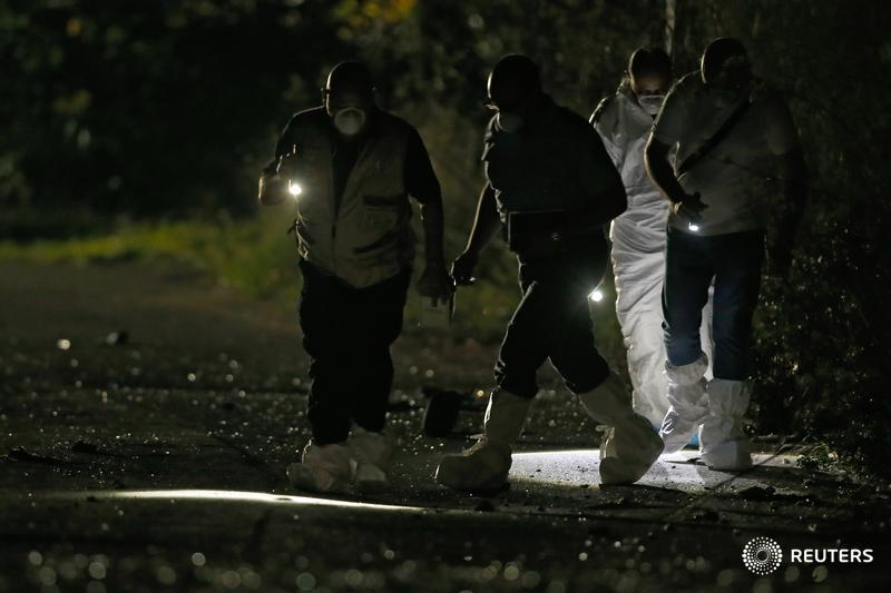Forensic experts use lights as they look for evidence on a road after a powerful bomb blew up a car killing investigative journalist Daphne Caruana Galizia in Bidnija