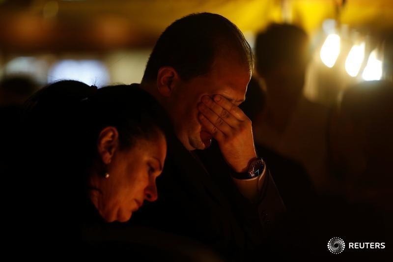 People react during a silent candlelight vigil to protest against the assassination of investigative journalist Daphne Caruana Galizia in a car bomb attack, in St Julian's