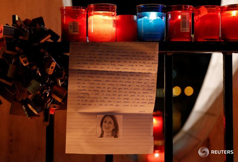 A letter to investigative journalist Daphne Caruana Galizia, assassinated in a car bomb attack on Monday, is seen on the Love monument during a silent candlelight vigil to protest against her murder, in St Julian's