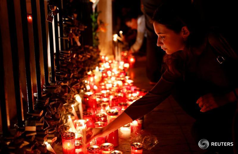 A woman places a candle on the Love monument during a silent candlelight vigil to protest against the assassination of investigative journalist Daphne Caruana Galizia in a car bomb attack, in St Julian's